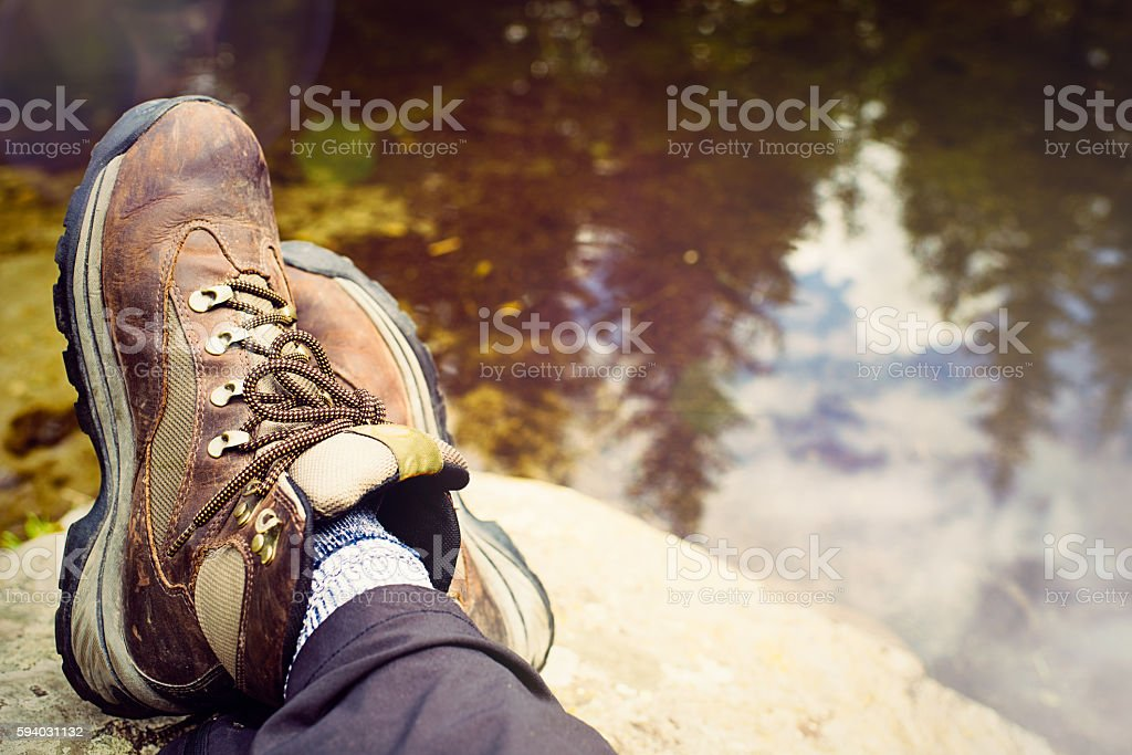 Female feet in hiking boots on rocks above lake stock photo