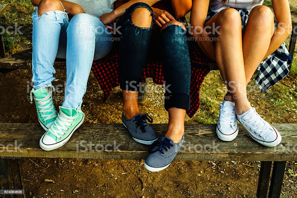 Female feet in jeans and sports shoes on a bench stock photo