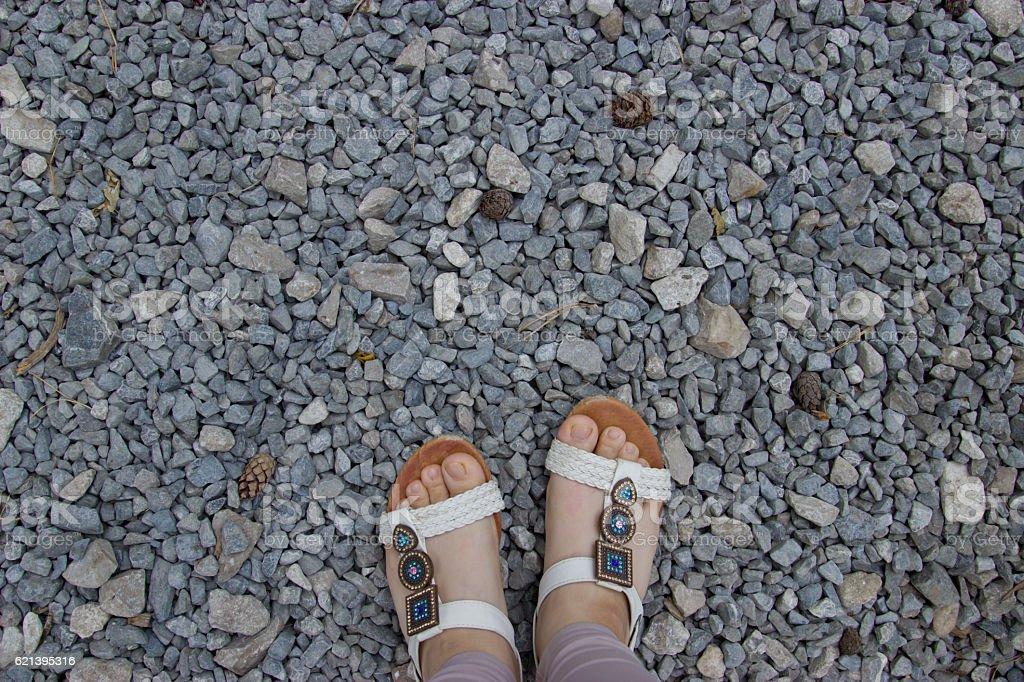 Female feet in sandals on gravel background. stock photo