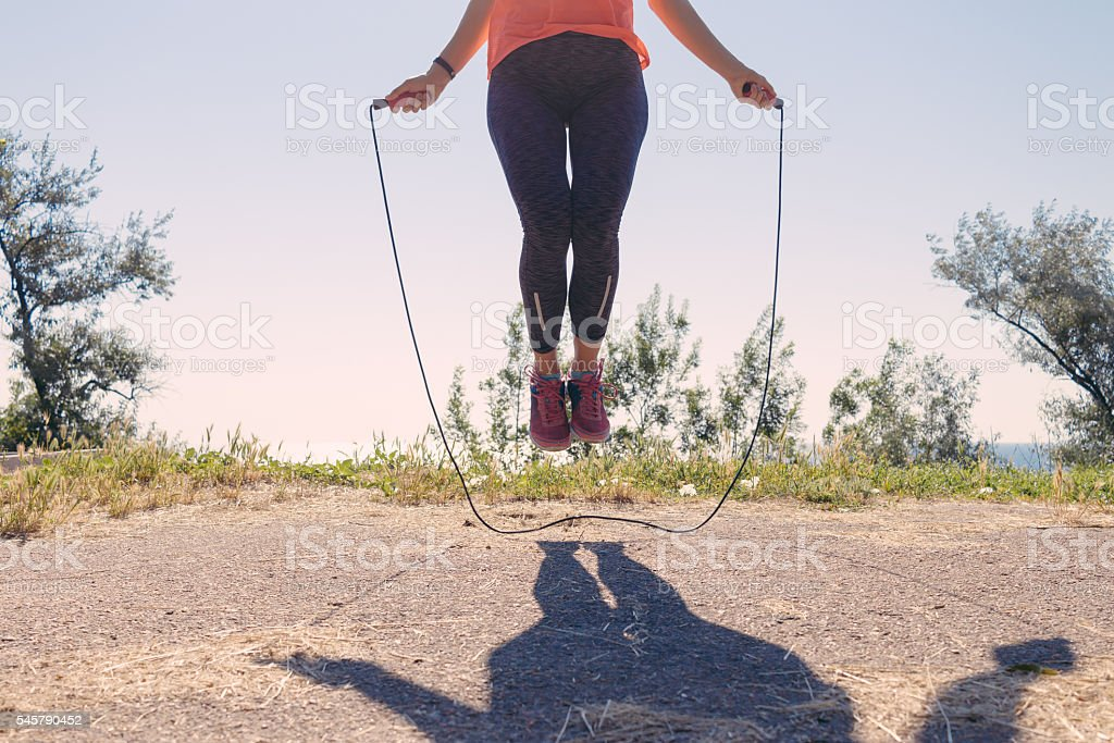 Female feet in sneakers jumping on a skipping rope stock photo