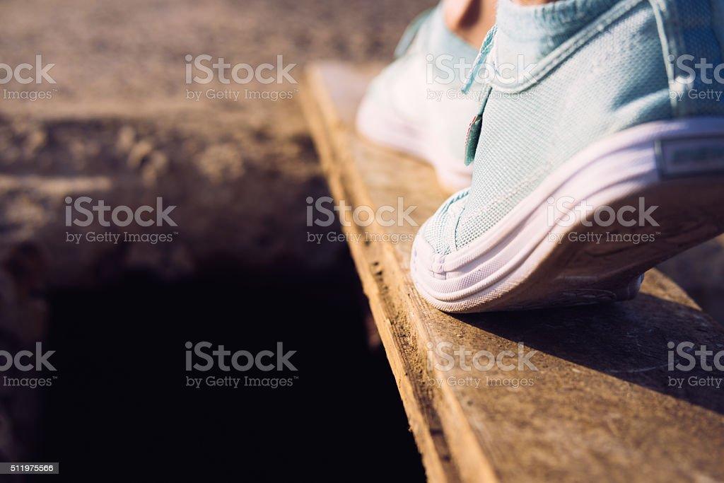 Female feet in sneakers walking on a narrow board stock photo
