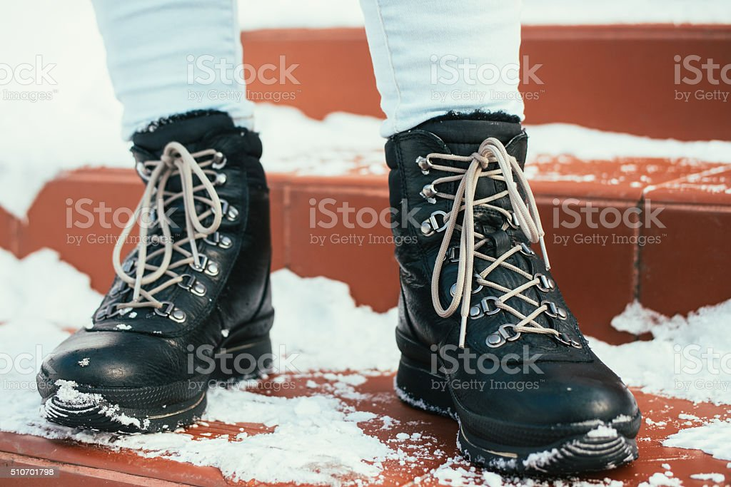 Female feet in winter boots with laces stock photo