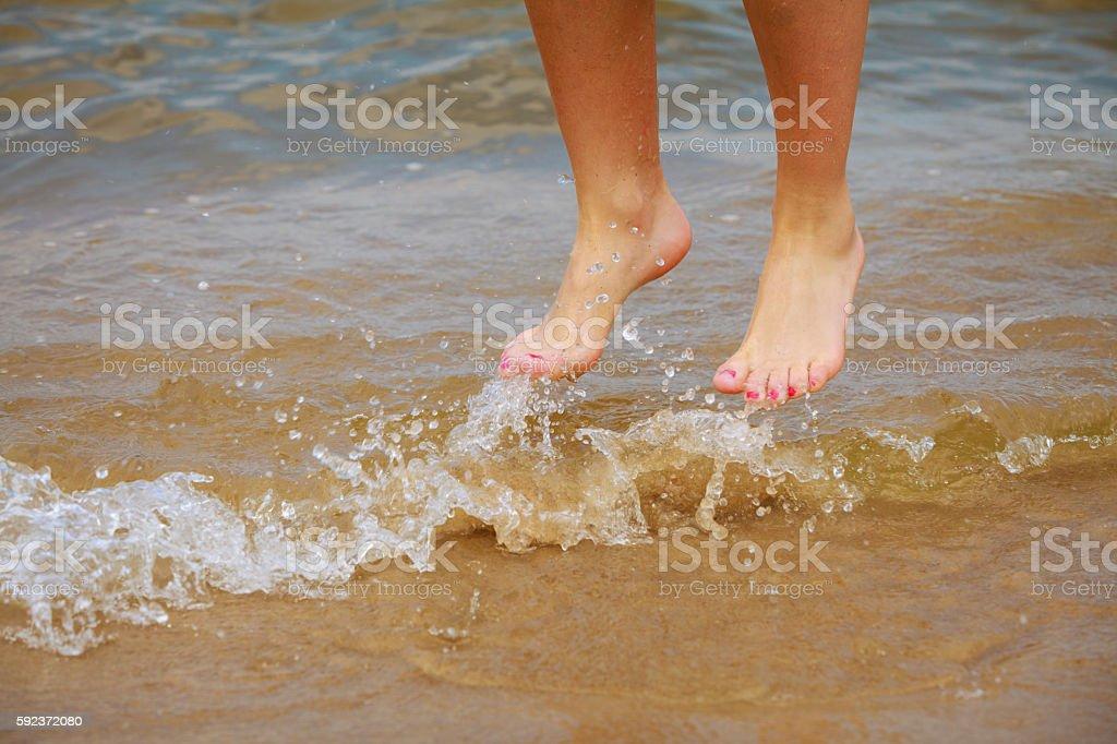 Female feet jump on beach. stock photo