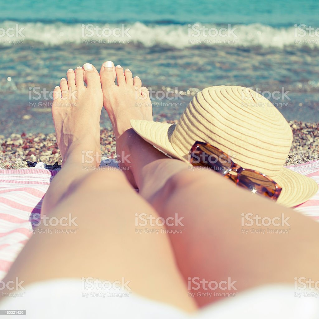 Female feet lying on sandy beach near sea stock photo