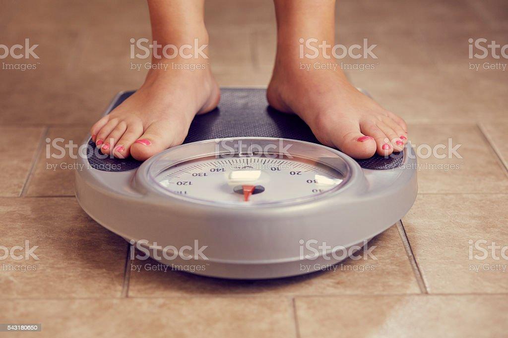 Female feet on a bathroom scale stock photo