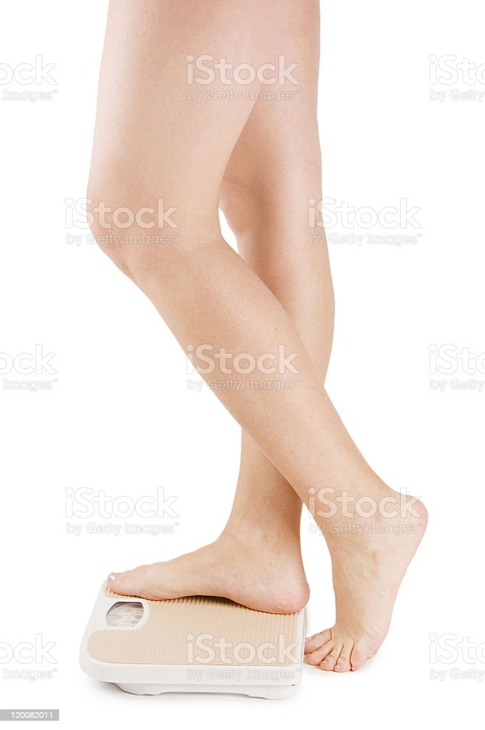 Female feet on scales isolated a white royalty-free stock photo