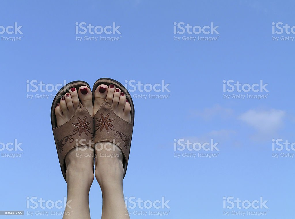 Female feet on summer sky background royalty-free stock photo
