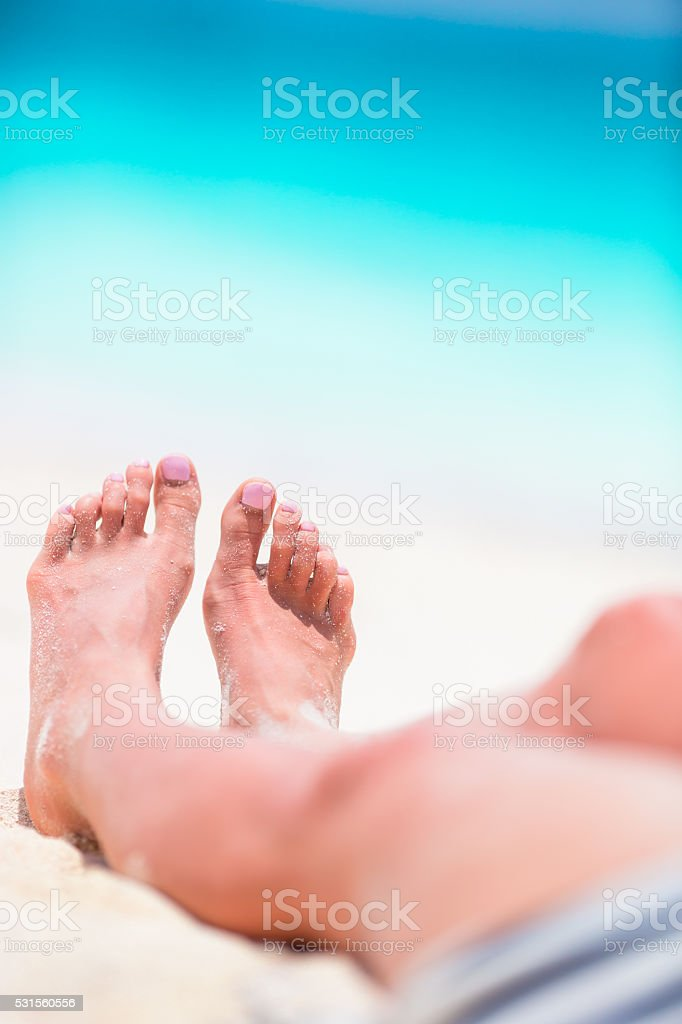 Female feet on the white sand beach in shallow water stock photo