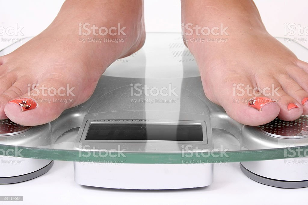 Female feet standing on a bathroom scale stock photo
