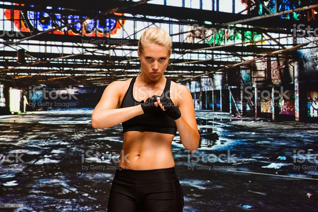 Female fighter in warehouse stock photo