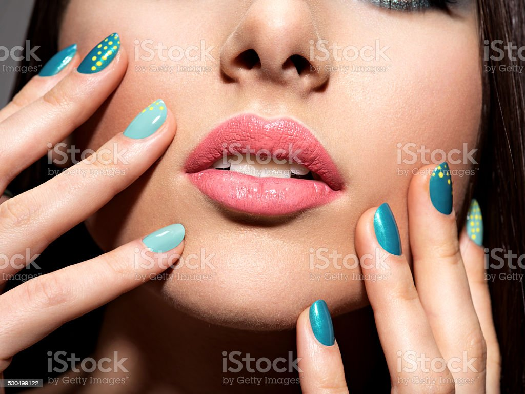 Female fingers with motton blue color stock photo
