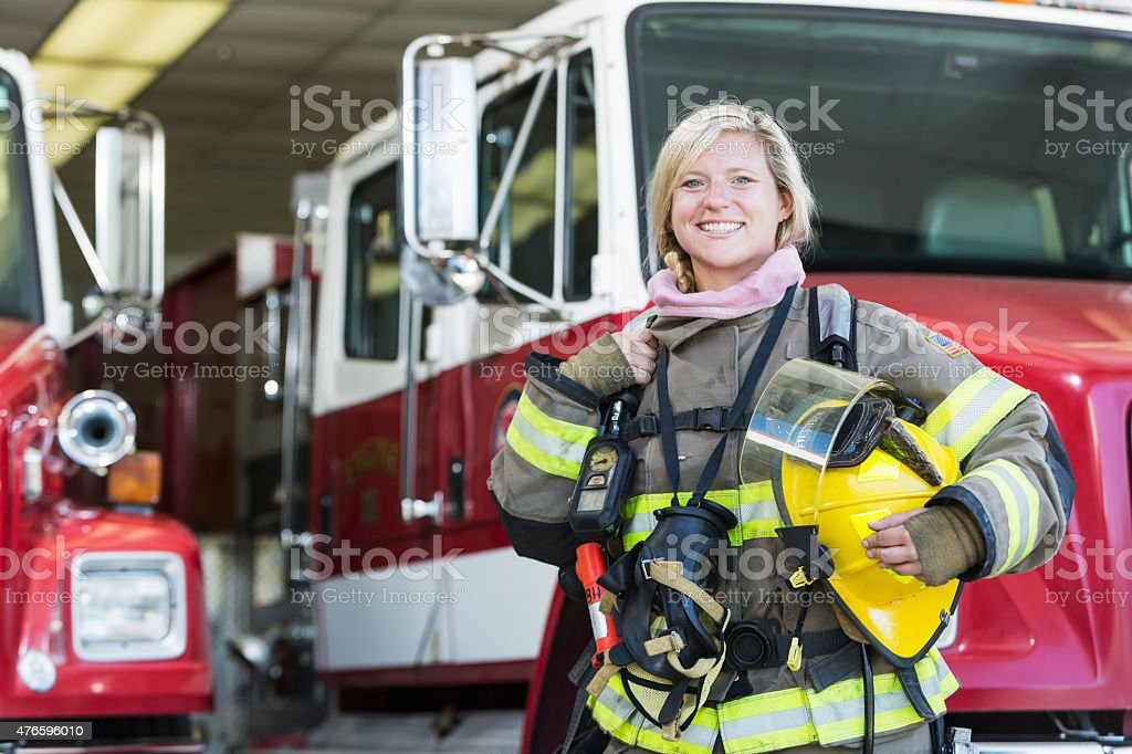 Female firefighter standing in front of fire truck stock photo