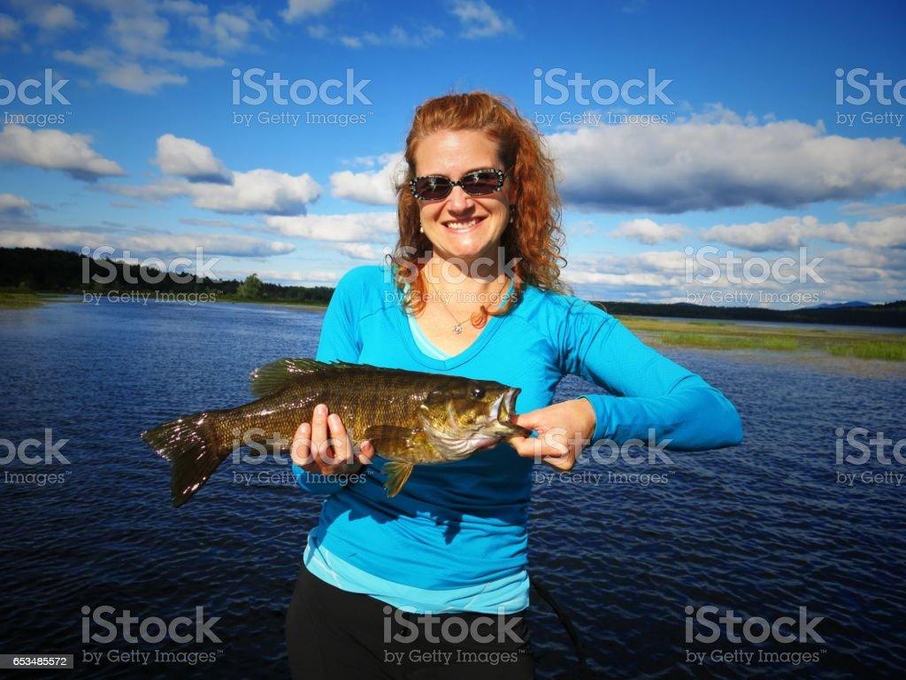 Female Fisherman Holding Caught Bass, Tupper Lake, NY stock photo