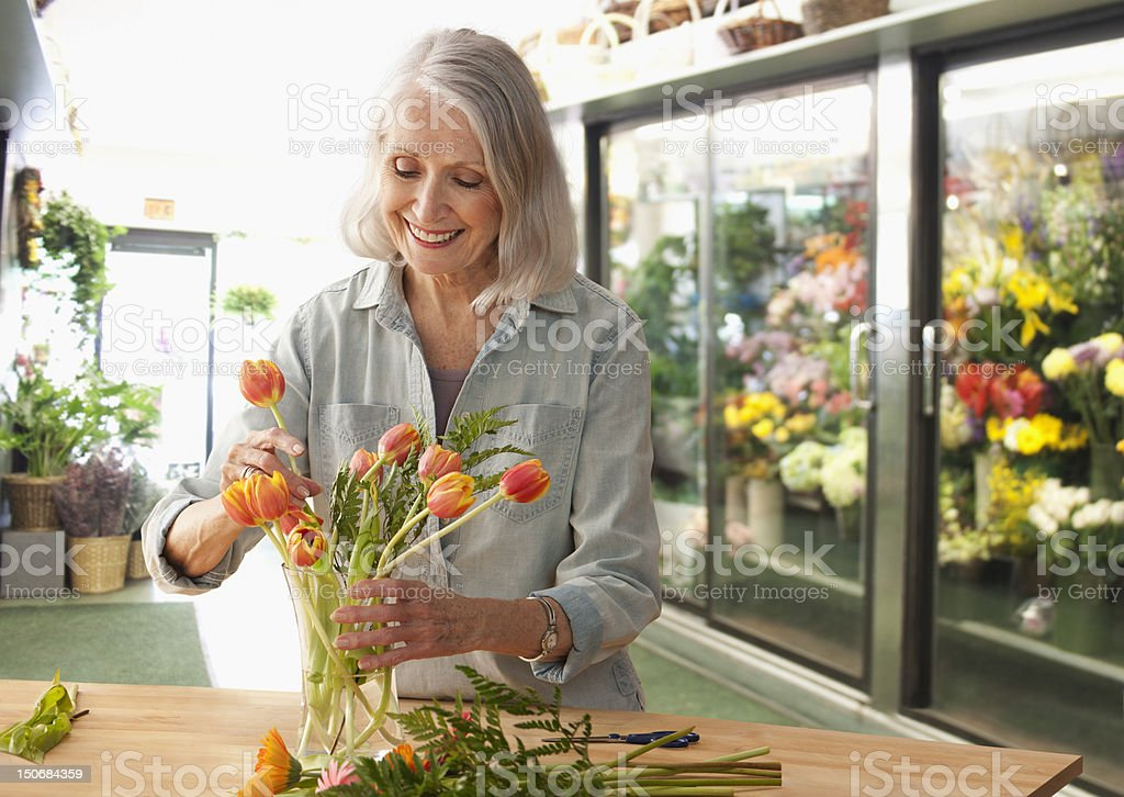 Female florist arranging flowers stock photo