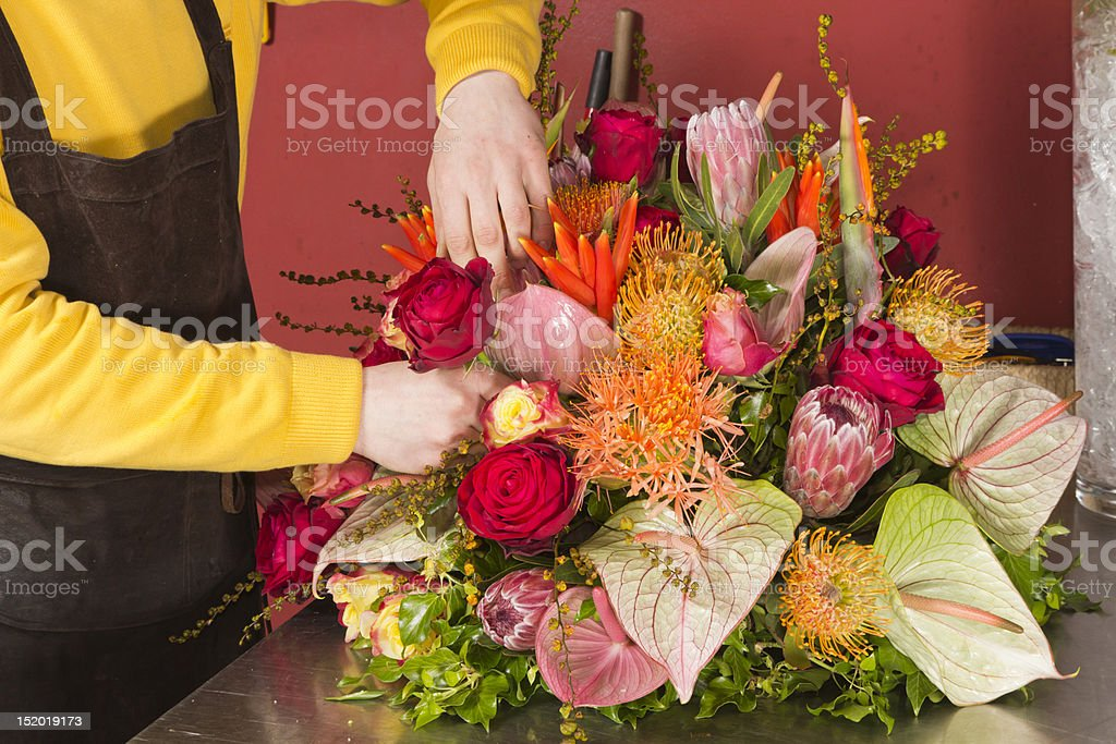 A female florist arranging her variety of flowers stock photo