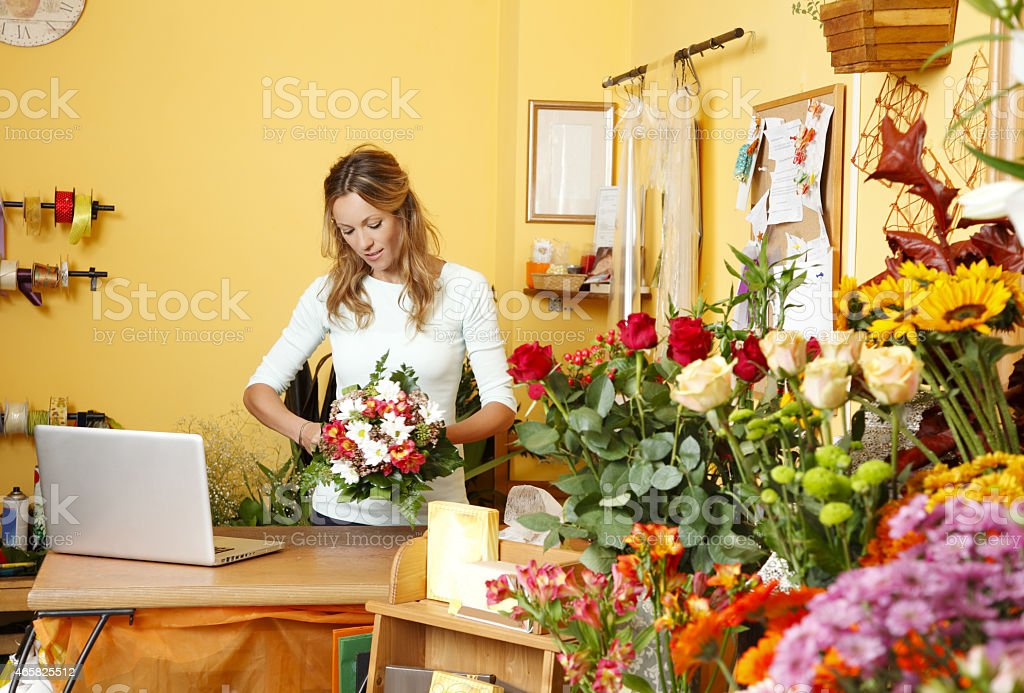 A female florist at work in her shop stock photo