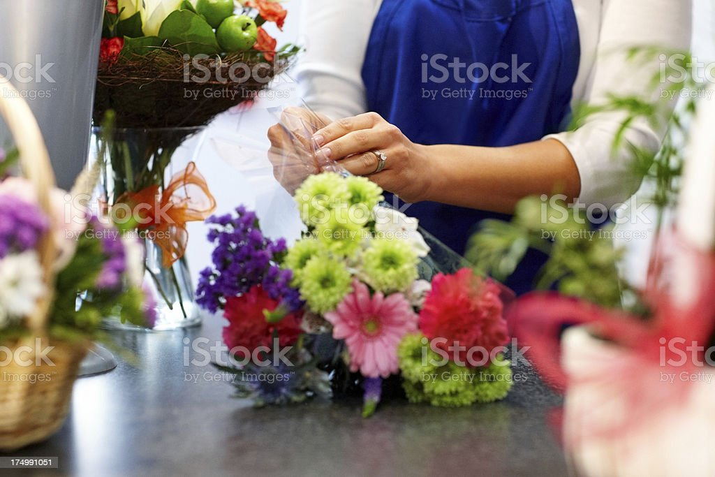 Female florist making bouquet in shop stock photo