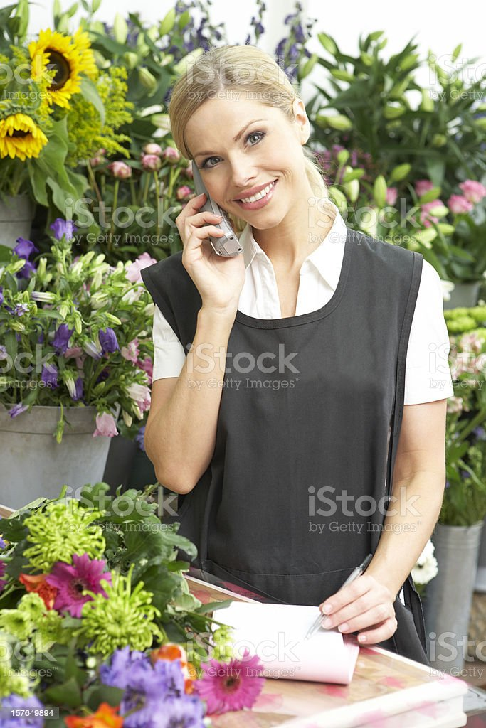 Female Florist Taking Telephone Order In Shop royalty-free stock photo