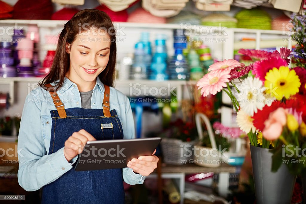 Female florist using tablet computer in flower shop stock photo