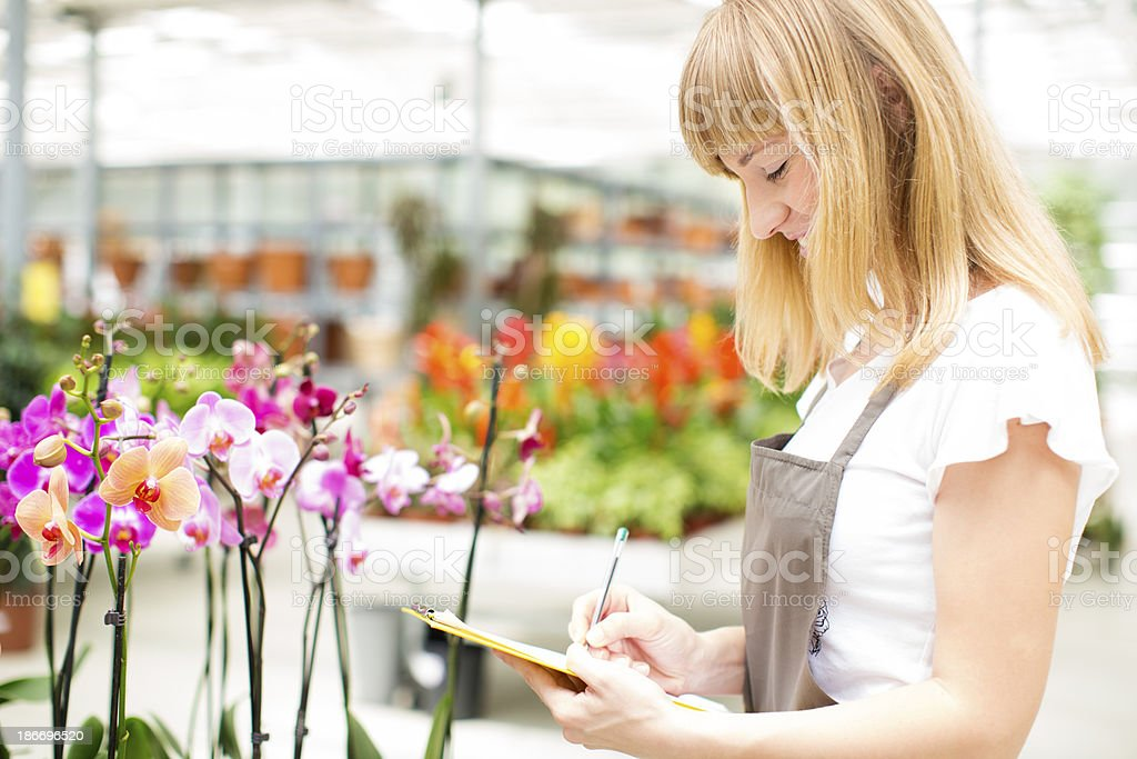 Female Florist Working At Garden Center. royalty-free stock photo