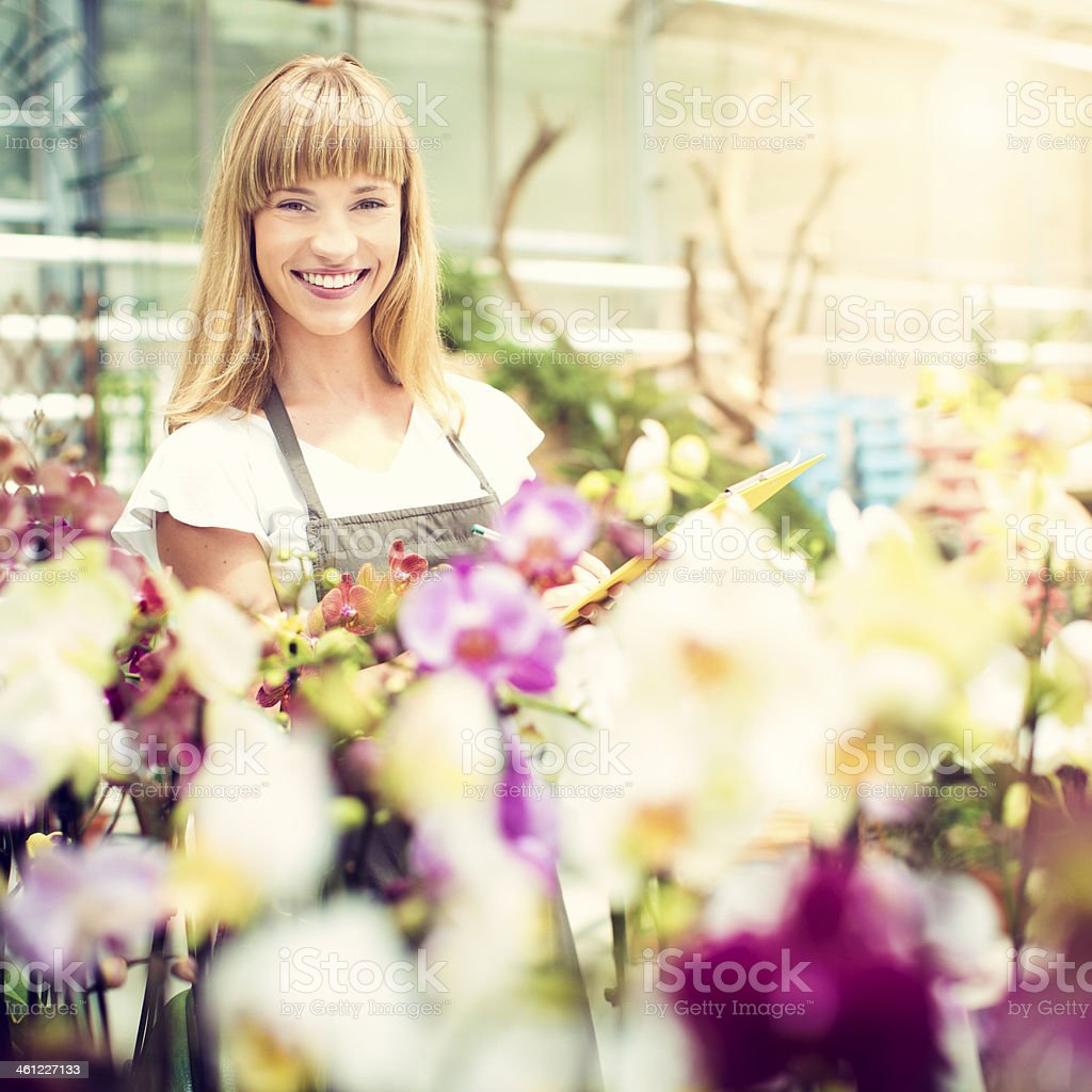 Female Florist Working At Garden Center. stock photo