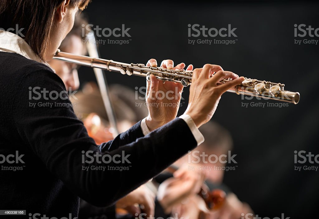 Female flutist with orchestra on stage stock photo
