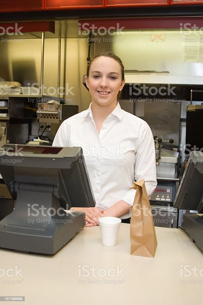 Female food service worker at counter with a coffee and bag royalty-free stock photo
