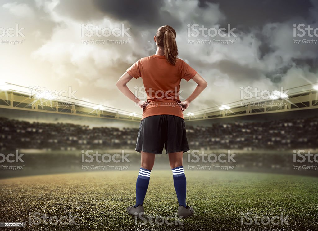 Female football player standing on the field stock photo