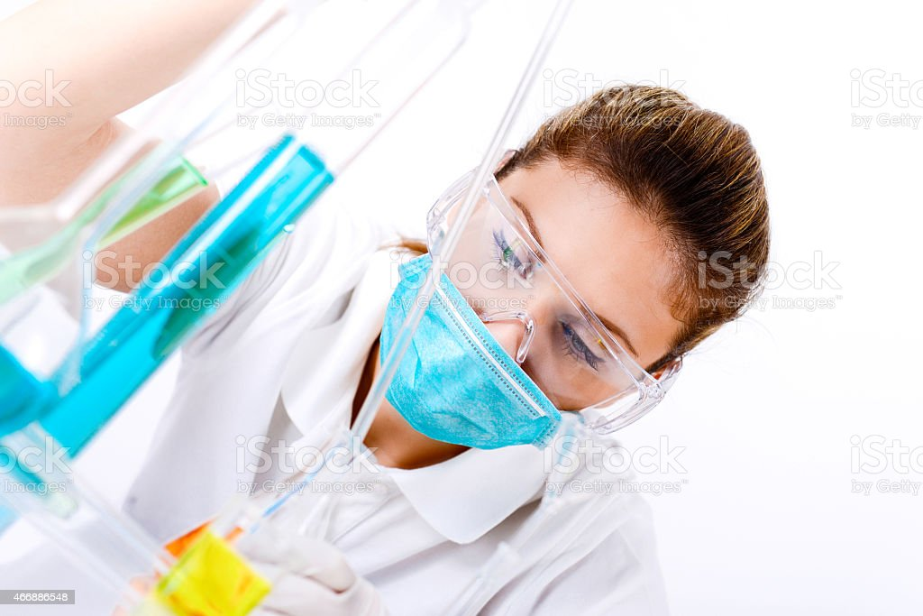 Female forensic scientist experimenting in laboratory with pipette and tubing stock photo