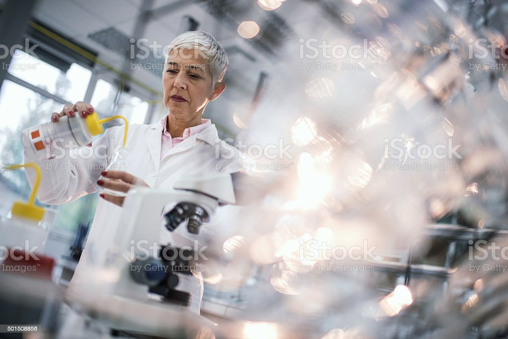 Female forensic scientist working on chemicals in laboratory. stock photo