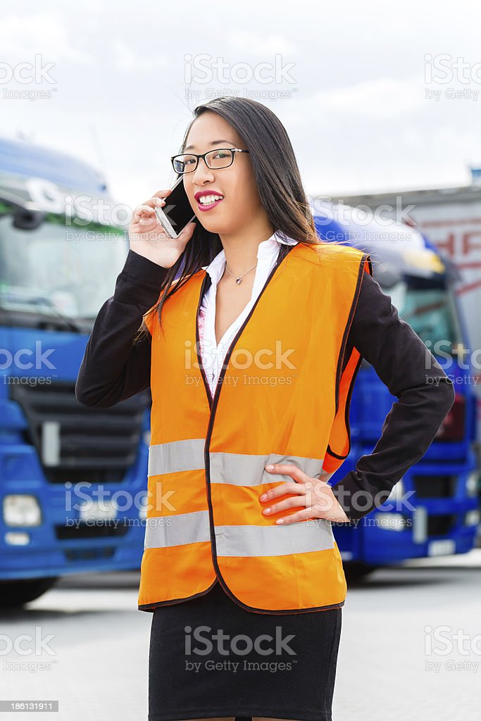 Female forwarder in front of trucks on a depot royalty-free stock photo