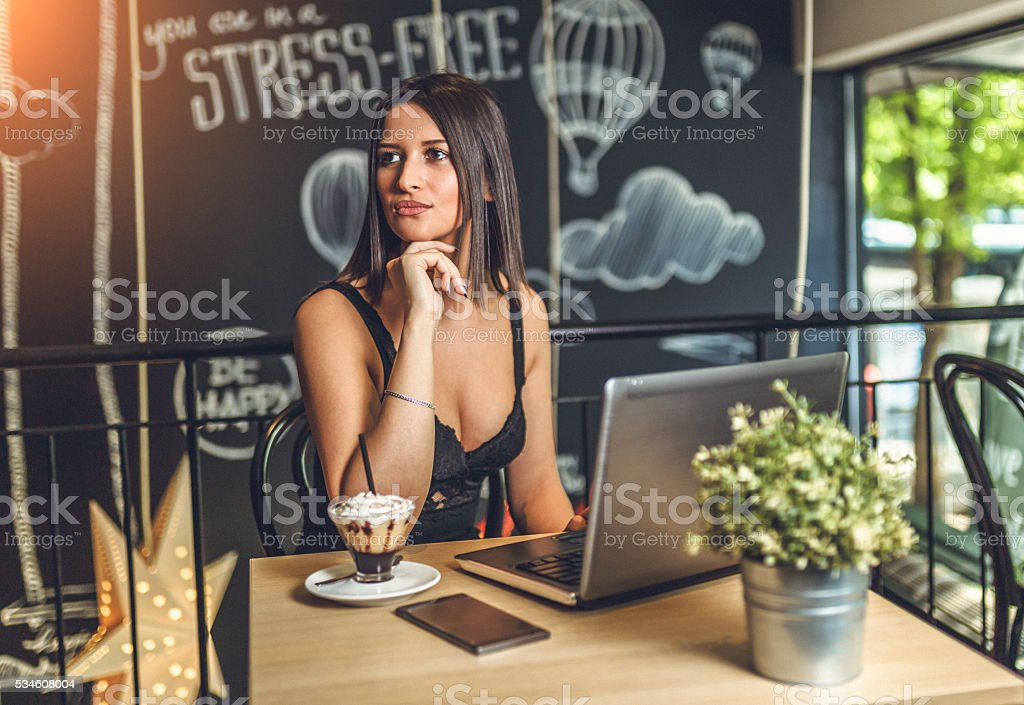 female freelancer sit at the table with net-book stock photo