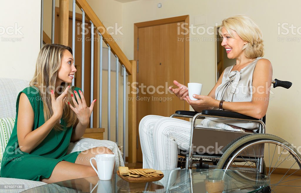 Female friend visiting disabled woman stock photo