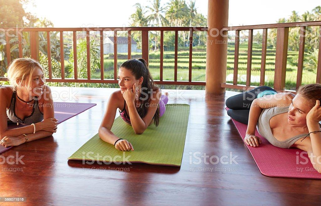 Female friends during yoga class break stock photo
