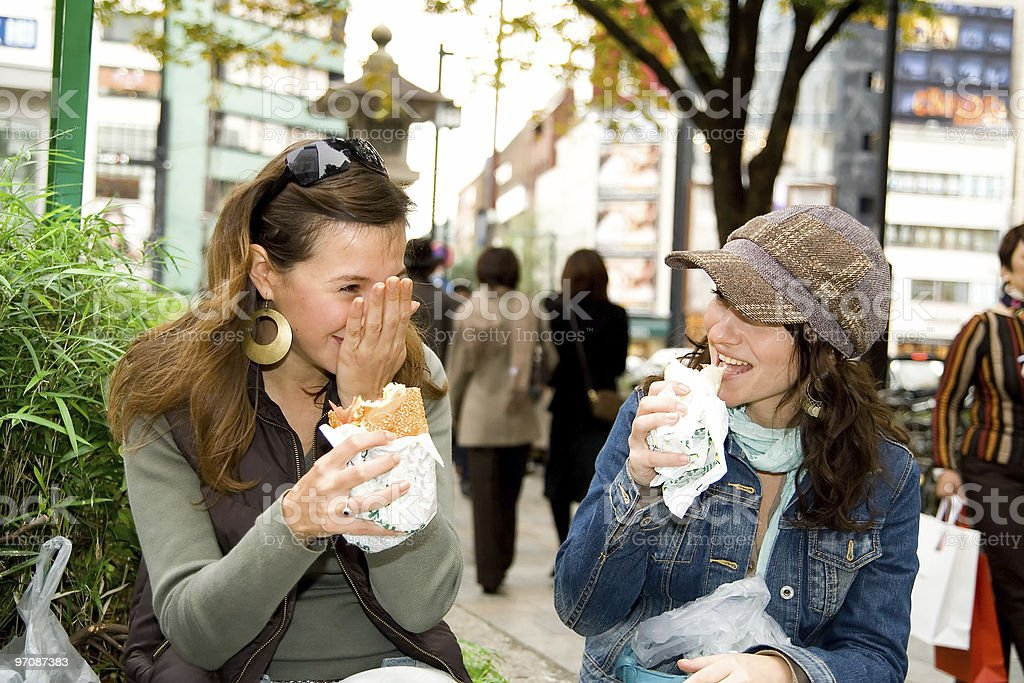 2 female friends eating burgers in a street royalty-free stock photo