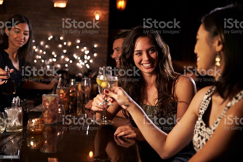 Female Friends Enjoying Night Out At Cocktail Bar stock photo