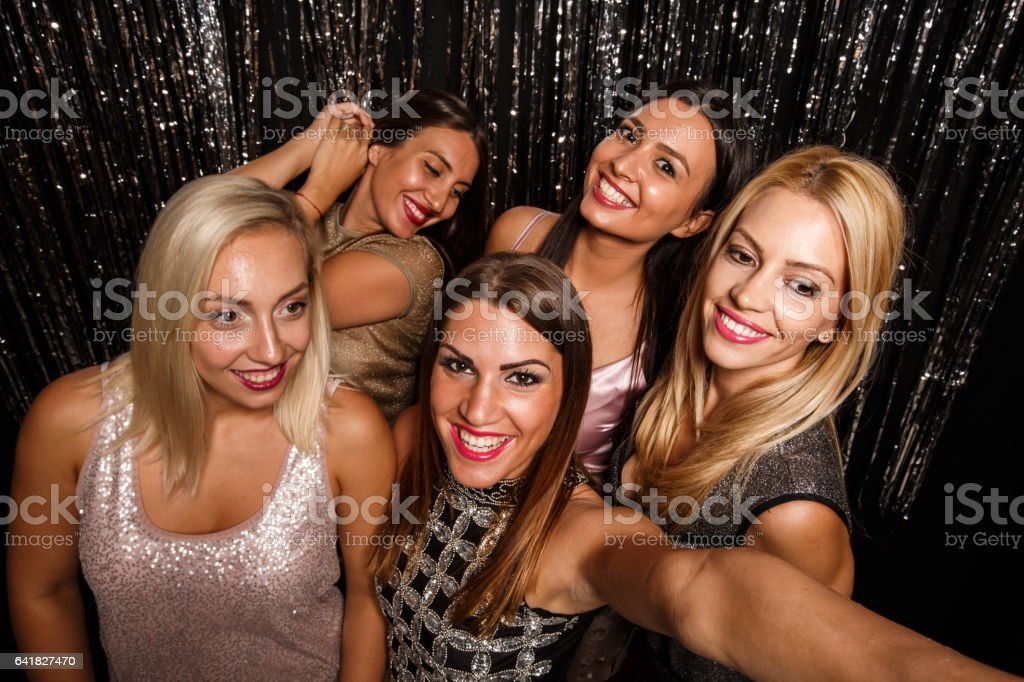 Female friends enjoying on dance floor at nightclub stock photo