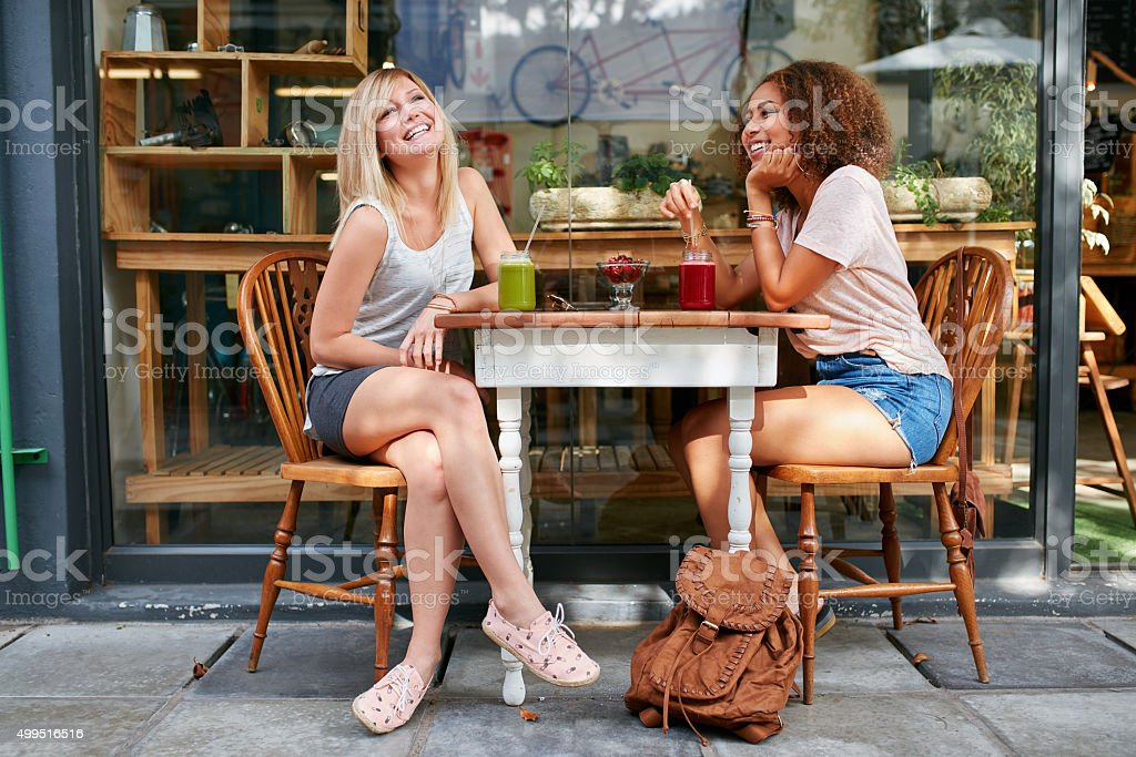Female friends hanging out at sidewalk cafe stock photo