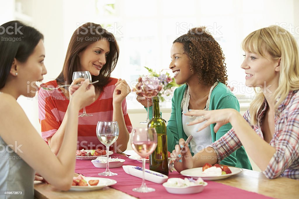 Female friends having dessert together at a table stock photo