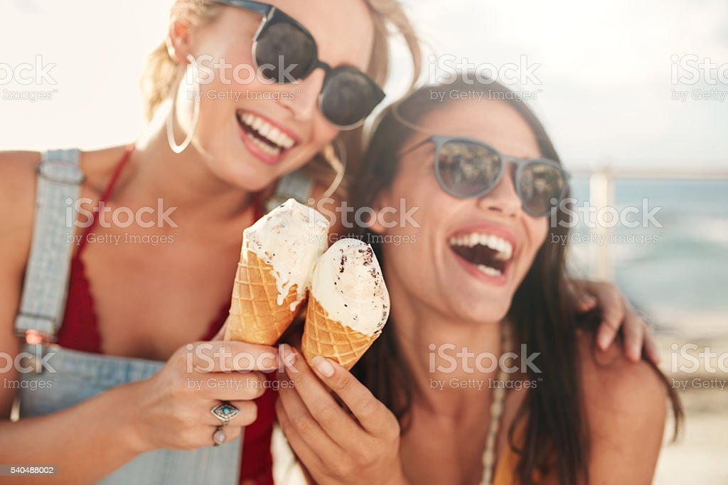 Female friends having fun and eating ice cream stock photo