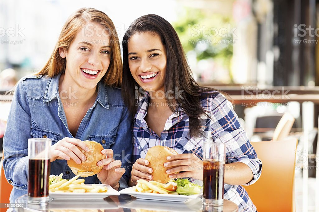 Female Friends Having Hamburgers At Cafe royalty-free stock photo