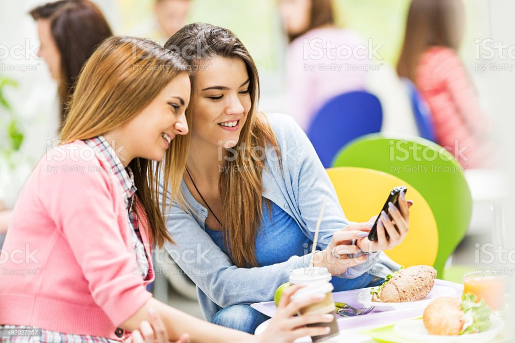 Female friends in a cafeteria text messaging. royalty-free stock photo