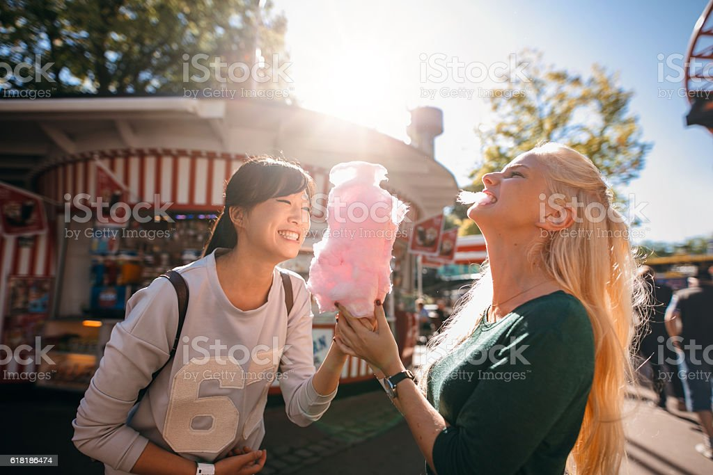 Female friends in amusement park eating cotton candy stock photo