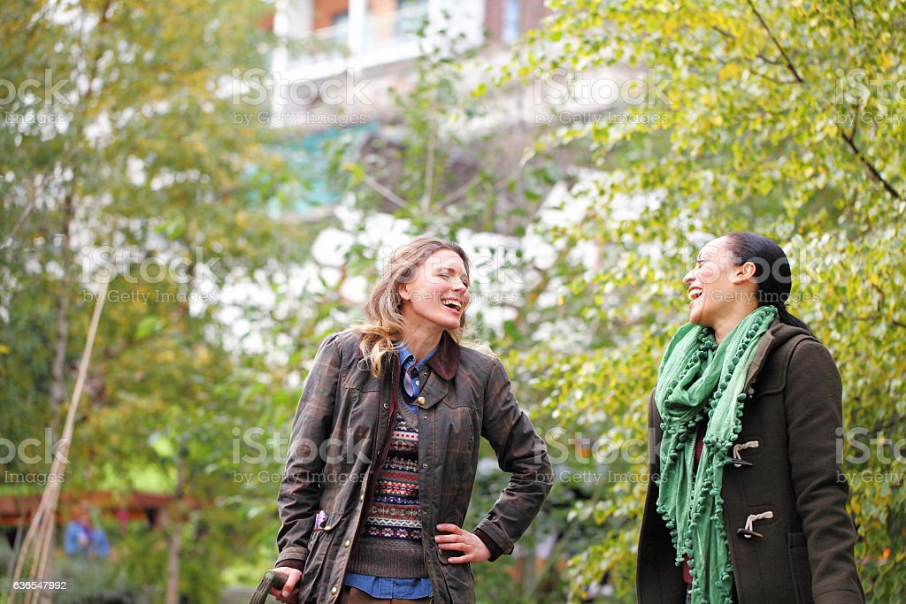 female friends laughing out loud in garden stock photo