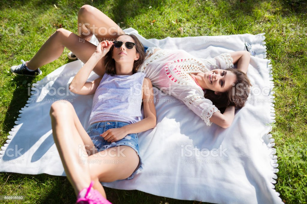 Female friends lying together on blanket in park stock photo