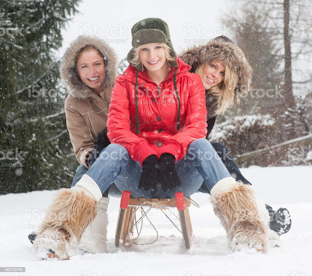Female Friends on a sled outdoor in the snow flakes stock photo