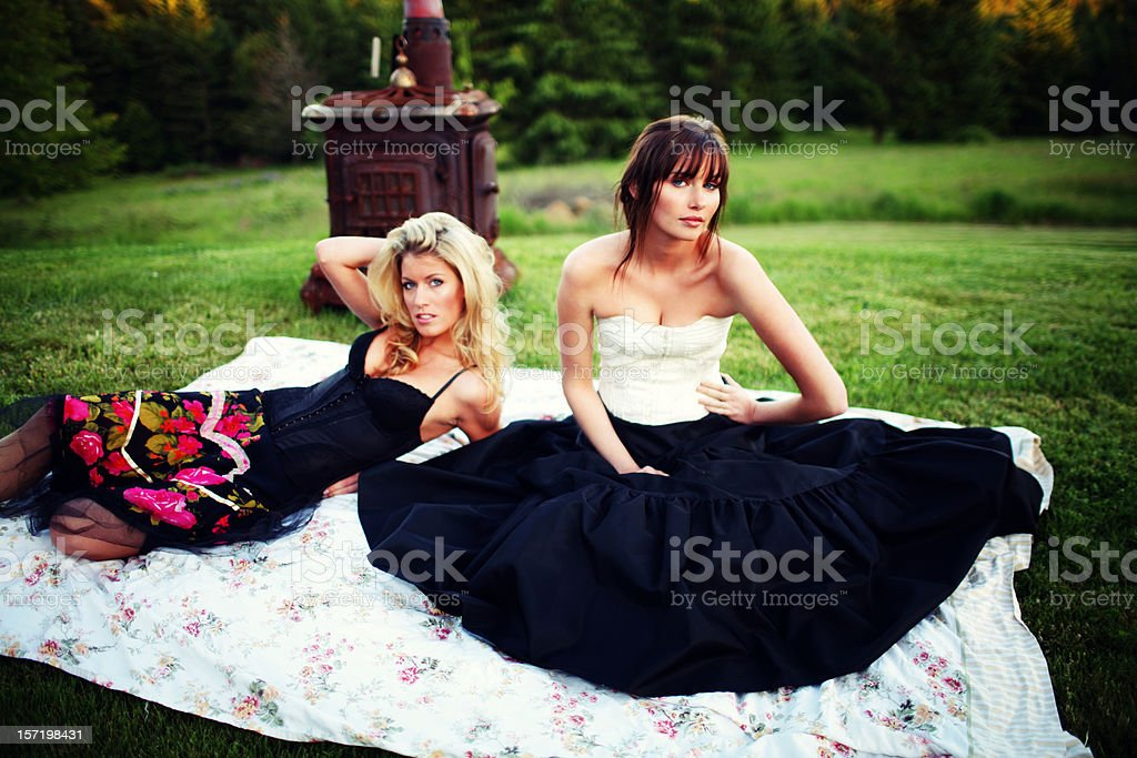Female Friends Outside with Old Fireplace and Blanket royalty-free stock photo