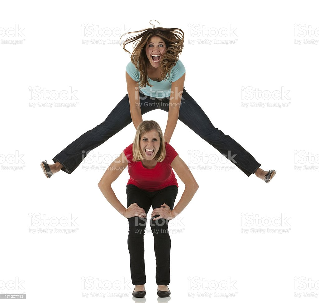 Female friends playing leapfrog stock photo