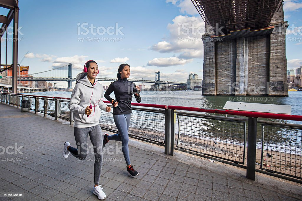 Female friends running along the east river stock photo