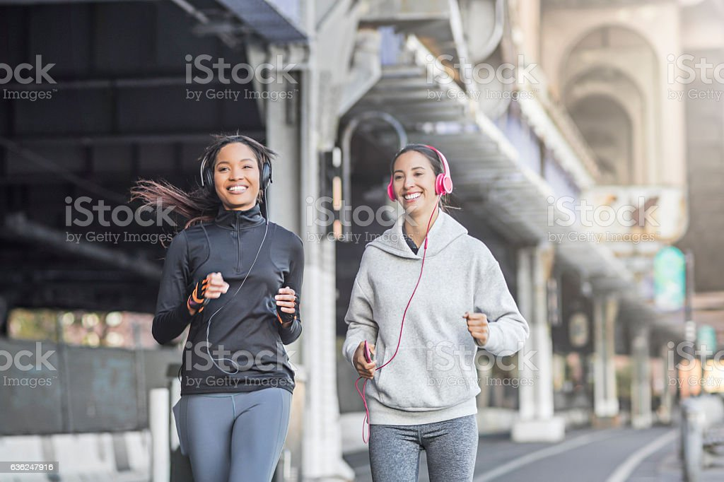 Female friends running on the city street stock photo